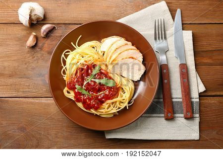 Delicious pasta with chicken parmesan slices and sauce on plate