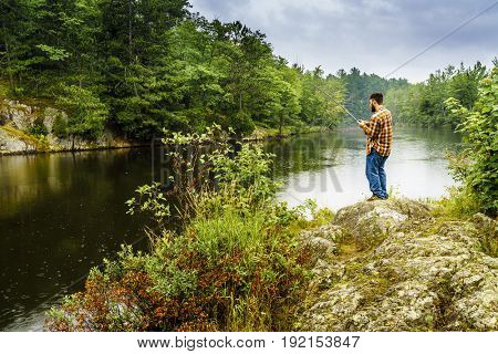 Upper Peninsula, Michigan, August 11, 2016: a dedicated angler is fishing on a river near Marquette, Michigan