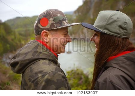 Young guy and girl in the mountains of Altai on the Katun River. Concept travel.