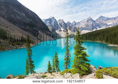 Beautiful turquoise waters of the Moraine lake with snow-covered peaks above it in Banff National Park of Canada