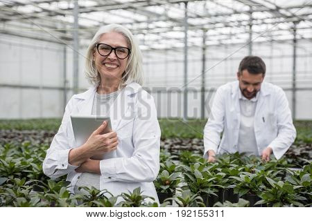 Picture of young man with mature woman standing in greenhouse near plants holding tablet computer. Looking at camera.
