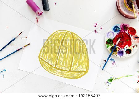 Child with a drawing of engineer safety helmet