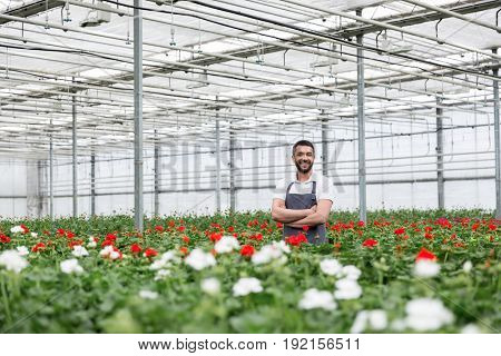 Photo of happy young man standing in greenhouse near plants. Looking aside.