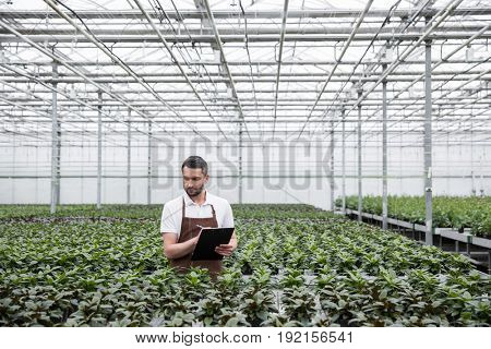 Image of young concentrated man standing in greenhouse near plants holding clipboard. Looking aside.