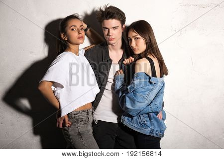 Image of concentrated young hipster man standing with friends women over gray background