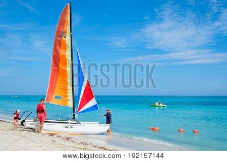 VARADERO,CUBA - JUNE 10,2017 : A family rides a colorful catamaran at the beautiful beach of Varadero in Cuba