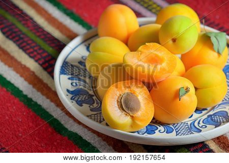 Ripe apricots fruits on rustic plate