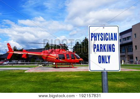 KALISPELL, MONTANA, USA - June 19, 2017: Physician parking only sign in front of an air ambulance at Kalispell Regional Medical Center