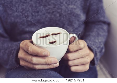 closeup of a young caucasian man having a cup of cappuccino with a happy face drawn with cocoa powder on the milk foam