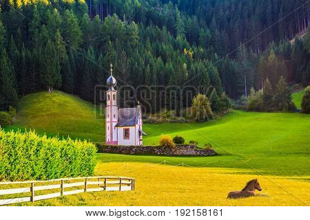 Chapel of St. Mary Magdalene and the bell tower in the valley of the Dolomites. The concept of eco-tourism in Tirol