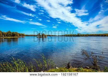 Incredible clouds over the Winnipeg River. Indian summer in Manitoba, Canada. Old Pinawa Dam Park. The concept of ecological and recreational tourism
