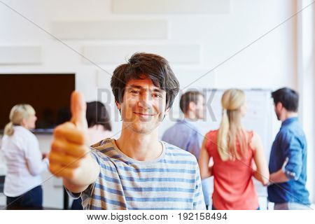 Happy young man holding thumbs up in front of his business team