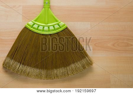 Closeup of new broom made of synthetic Nylon fiber with green handle on wooden background with copyspace