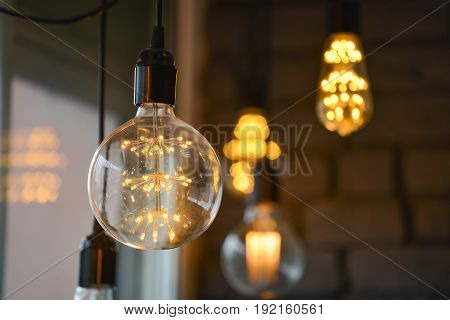 Big Glowing Led filament cob lamps, blured lights at background, bokeh
