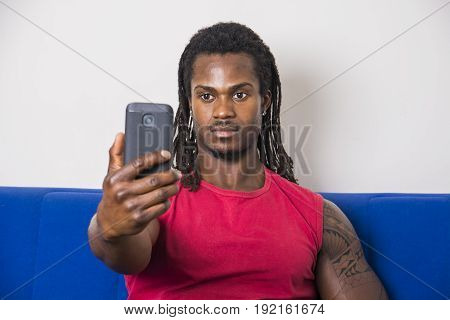 Handsome black muscular bodybuilder man taking selfie with cell phone while laying on couch