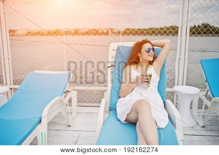 Portrait Of An Amazing Young Girl Wearing Sunglasses Enjoying Her Cocktail Sitting On A Lounger In L