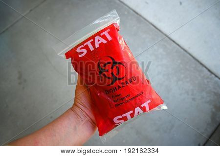Biohazard bag containing ice and refrigerated medication
