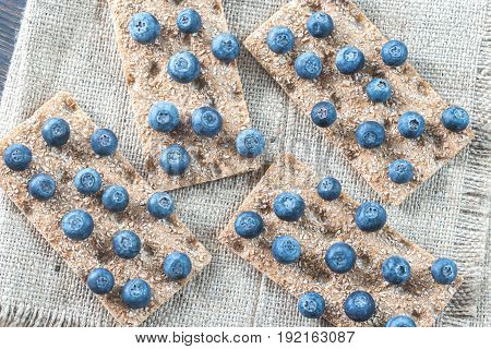 Crispbread with fresh blueberries on the burlap: top view