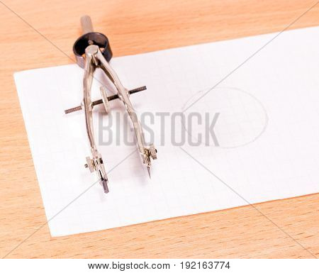 Tool and drawn circle metal wirkul with a needle and a pencil on a wooden background