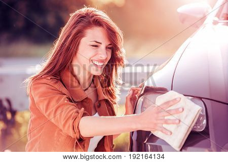 Young woman cleaning his car outdoors. Woman with a microfiber wipe the car polishing.