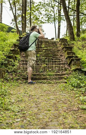 Tourist with a backpack makes summer forest pictures in the park on the retro camera walking through the old cobbled path and stairs in the moss.