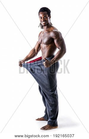Shirtless black male bodybuilder has lost weight, wearing large pants and stretching them to see his progress