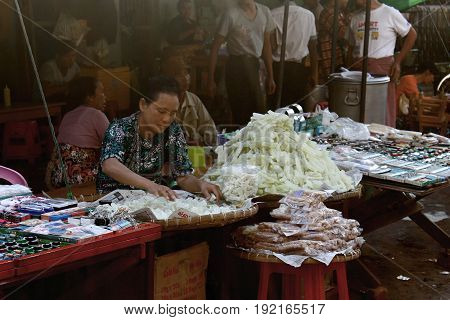 ZEGYO MARKET/MANDALAY, MYANMAR JAN 22: A Women selling some sort of tailor's chalk is gently arranging her goods in the sewing supply section of the Zegyo Market January 22, 2016, Zegyo Market, Mandalay.