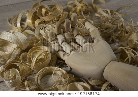 Hand of a wooden puppet lying in sawdust on the table.