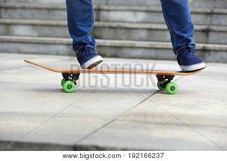 closeup of skateboarder legs skateboarding at city