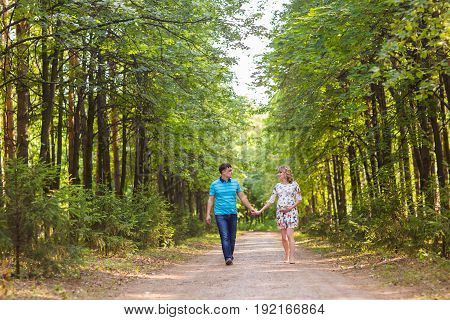 happy young pregnant woman with her husband walking in a park.