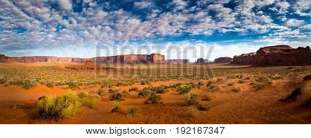 Monument Valley Panorama at Sunrise with Clouds and scrub brush.