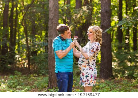 Pregnancy, family, happiness and fun concept - Man and pregnant woman have fun with candy in the park.