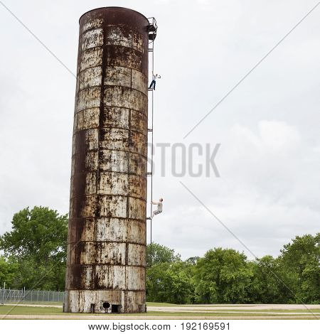 image of a caucasian father and grown son spending time together climbing up the ladder of a very tall old and rusted water tower which is dangerous and risky.