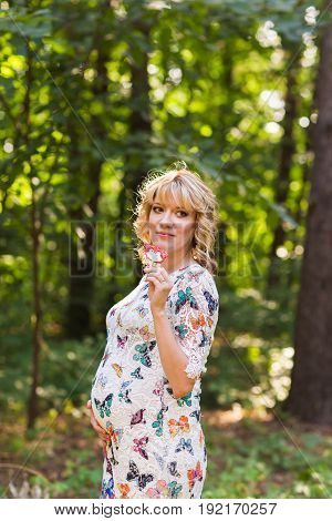 Outdoor portrait of young pregnant woman holding a lollipop in summer nature.