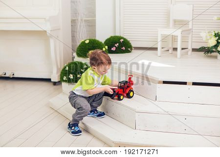Little boy is playing with toy car at home.