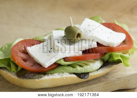 open baguette whit Mexican Panela cheese, tomato, lettuce, salt, pepper and olives at the top