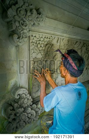 BALI, INDONESIA - MARCH 08, 2017: Man using a chisel to do art on a wall of cement, in Denpasar Bali located in Indonesia.