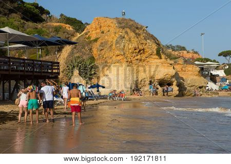 ALBUFEIRA, PORTUGAL - AUGUST 24, 2016: People at the famous beach of Olhos de Agua in Albufeira. This beach is a part of famous tourist region of Algarve.