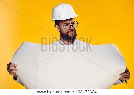 Businessman in a helmet, businessman in glasses, businessman on a yellow background.