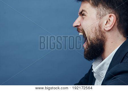 Businessman screaming, businessman with a beard, businessman on a blue background.