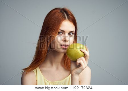 Woman with apple, woman holding apple on gray background.
