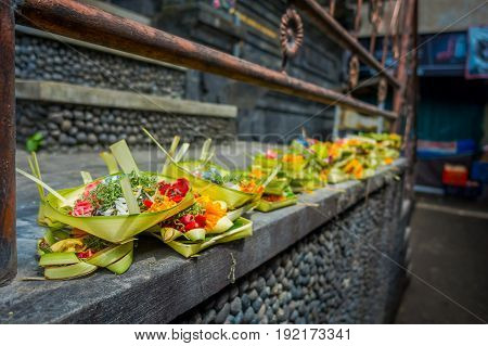 A market with a box made of leafs, inside an arrangement of flowers on a stone table, in the city of Denpasar in Indonesia.