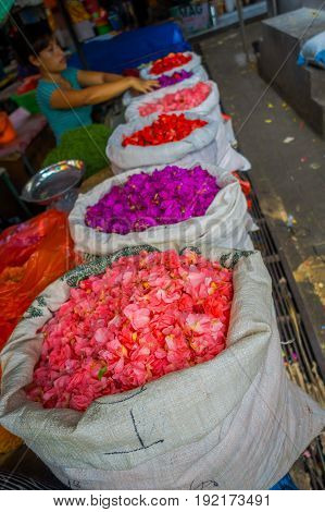 BALI, INDONESIA - MARCH 08, 2017: Unidentified people in outdoors Bali flower market, white sacks in row, flowers are used daily by Balinese Hindus as symbolic offerings at temples, inside of colorful baskets.