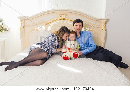 Portrait of happy family sitting together on bed in bedroom at home