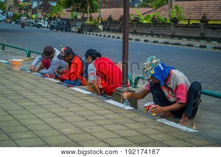 BALI, INDONESIA - MARCH 08, 2017: Unidentified group of people painting the sidewalk outside of the royal temple of Mengwi Empire located in Mengwi in Bali, Indonesia.