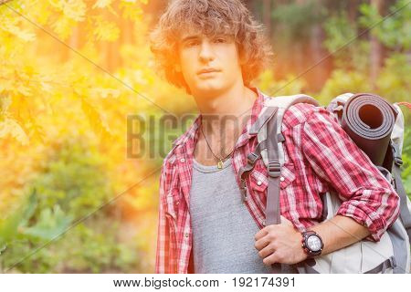 Young male hiker with backpack looking away in forest