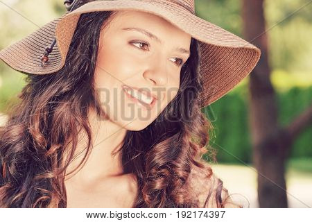 Smiling young woman in sunhat looking away in park