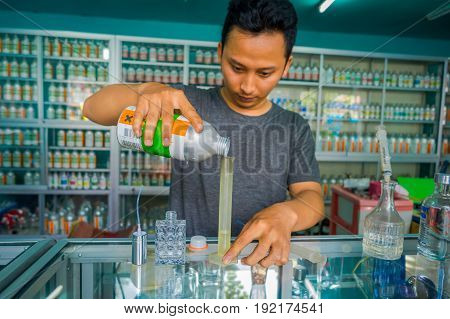 BALI, INDONESIA - MARCH 08, 2017: Unidentified man using syringes and pipettes mixing essences to prepare perfumes for the perfume store in Denpasar Indonesia.