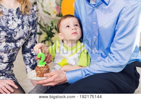 family, parenthood, happy birthday and holiday concept - close-up happy parents and child at a table drinking tea and eating cake
