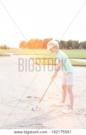 Middle-aged woman playing golf at course against clear sky